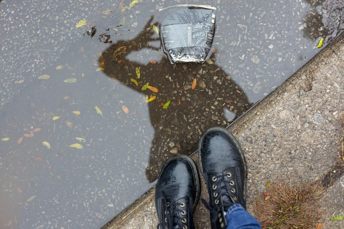 Mensch schaut seinen Schatten an und sieht Müll statt Kopf